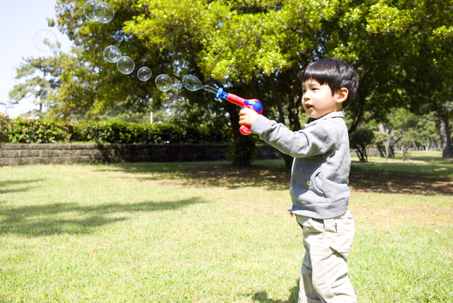 シャボン玉で遊ぶ3歳の子供