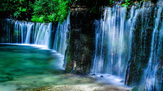 新緑をバックに流れ落ちる滝の姿