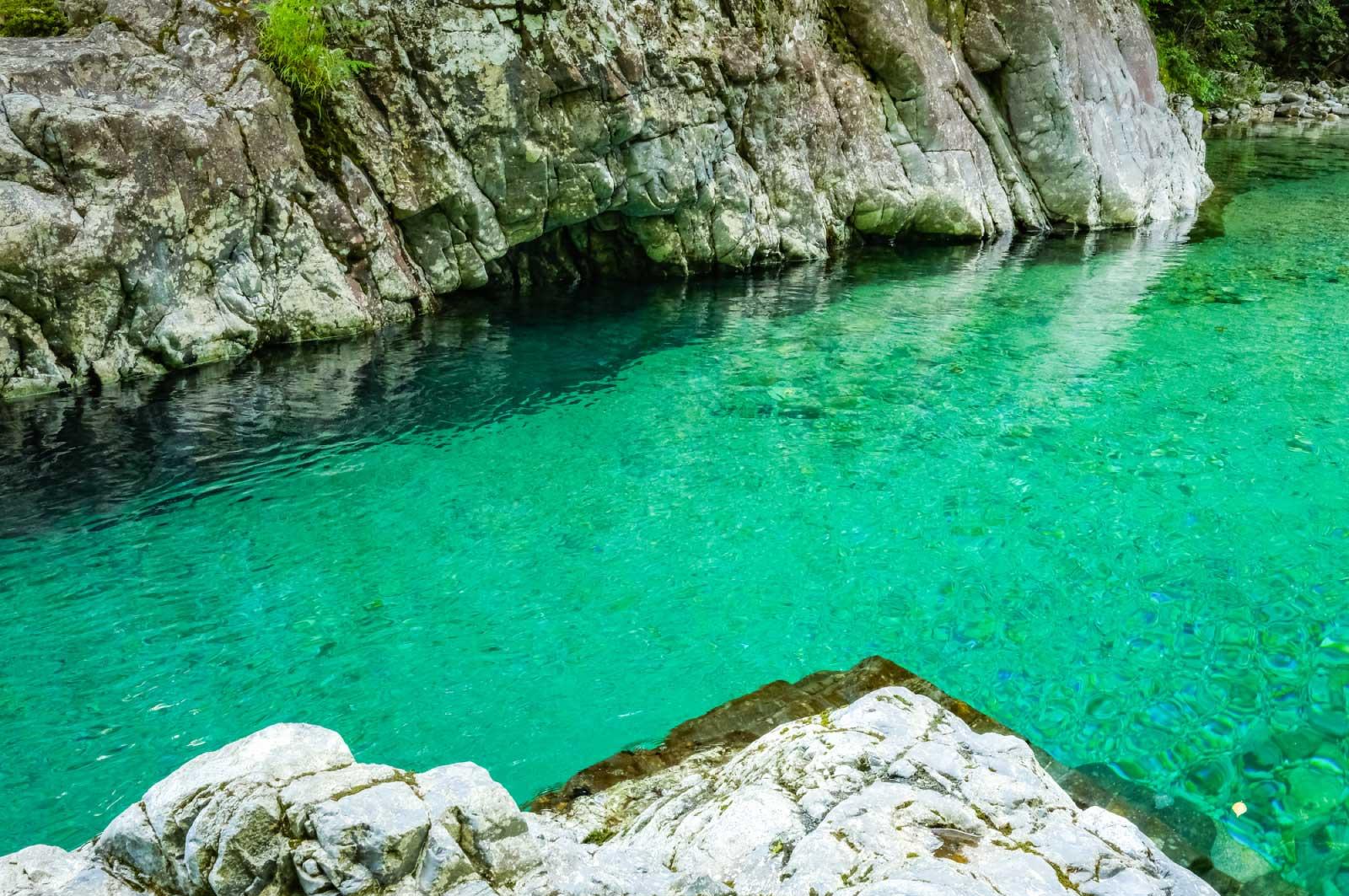 透明でエメラルドグリーンの水が流れる渓谷