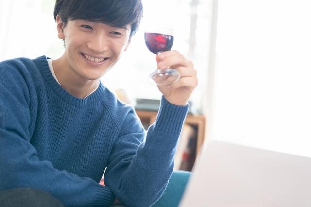 自宅でワインを飲む男性
