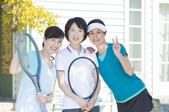 テニスをする50代女性