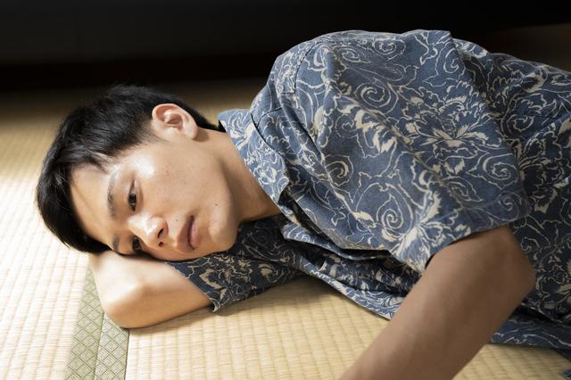 畳でゴロゴロする男性