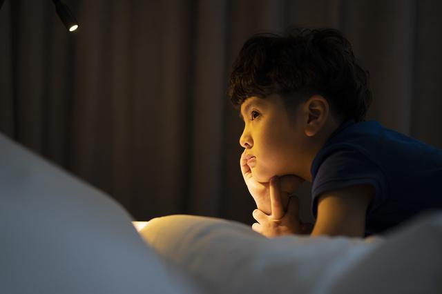暗い部屋で留守番する子供